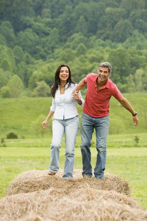 Portrait Of A Man And A Woman Running On Hay Bales