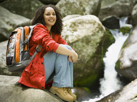 Portrait Of A Young Woman Sitting On A Rock And Smiling