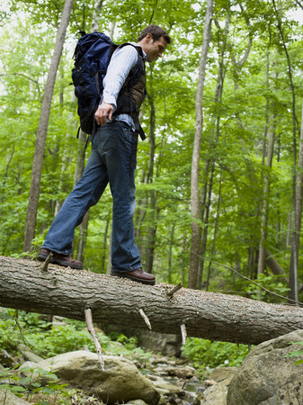 Low Angle View Of A Young Man Walking On A Fallen Tree