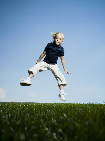 Low Angle View Of A Girl Jumping And Smiling LANG_EVOIMAGES