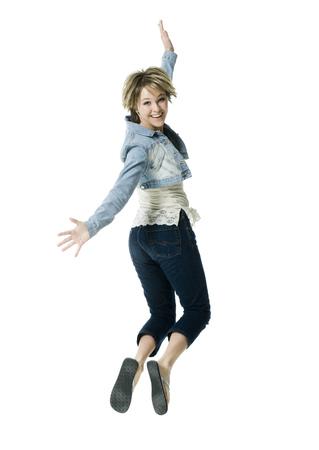 Retrato de una mujer joven saltando en medio del aire