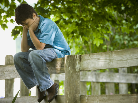 Profile Of A Boy With His Hands On His Face Sitting On A Wooden Fence