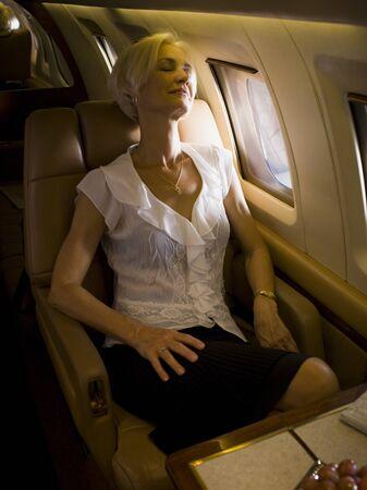 A Senior Woman Sleeping In An Airplane