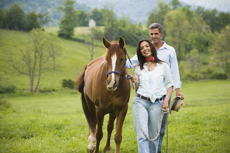 Man And A Woman Walking With A Horse LANG_EVOIMAGES