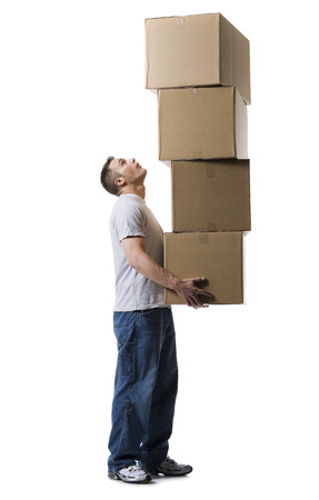 over burdened: Profile Of A Young Man Holding A Stack Of Cardboard Boxes LANG_EVOIMAGES