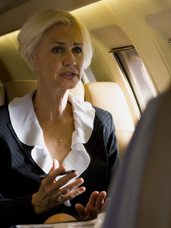 A Businesswoman And A Businessman Talking In An Airplane