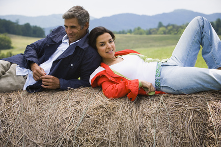 Portrait Of A Woman And A Man Resting On A Hay Bale