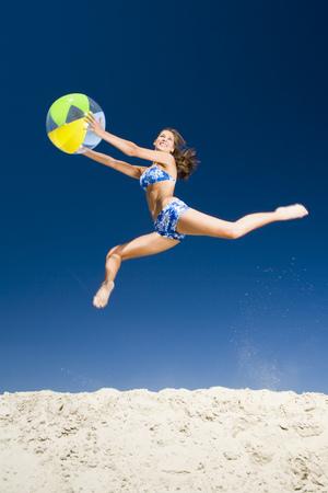 elasticidad: Joven mujer sosteniendo una pelota de playa y saltando