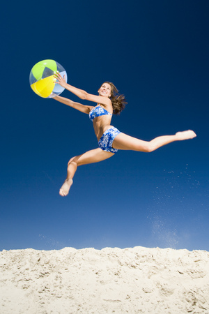 Young Woman Holding A Beach Ball And Jumping