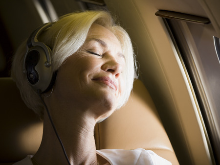 Close-Up Of Senior Woman Wearing Headphones And Sleeping In An Airplane