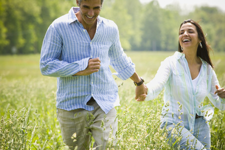 Man And A Woman Holding Hands And Running In A Field