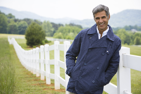 one mature man only: Portrait Of A Man Leaning Against A Fence