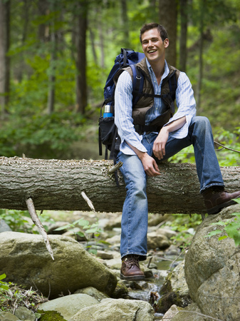 Portrait Of A Young Man Sitting On A Fallen Tree LANG_EVOIMAGES