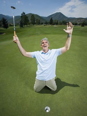 move in: Man Kneeling Near A Golf Hole With His Arms Raised LANG_EVOIMAGES