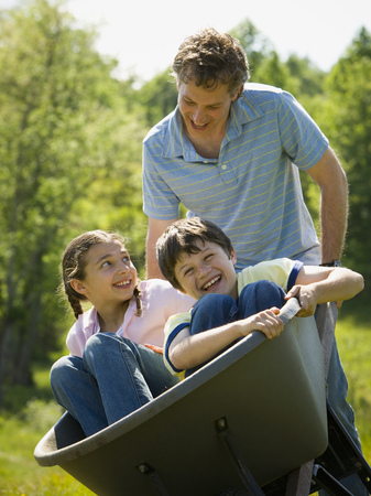 Man Pushing His Son And Daughter In A Wheelbarrow