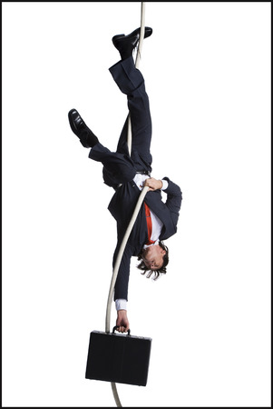 Businessman With Briefcase Dangling Upside Down From A Rope