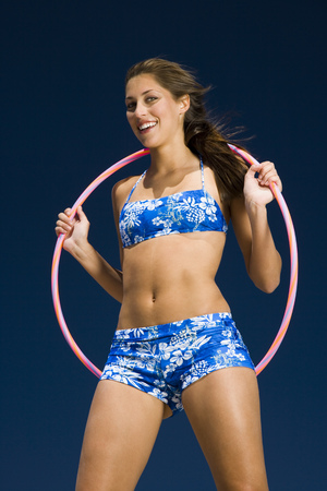 Portrait Of A Young Woman Holding A Hula Hoop And Smiling LANG_EVOIMAGES