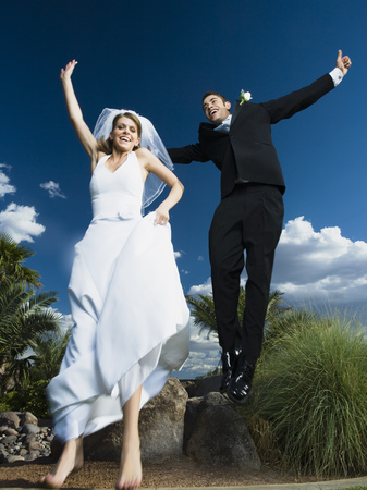 ebullient: Low Angle View Of A Newlywed Couple Holding Hands And Jumping LANG_EVOIMAGES
