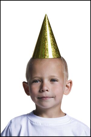 Young Boy With Party Hat Holding Hands Behind Back LANG_EVOIMAGES