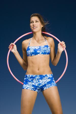 Retrato de una mujer joven sosteniendo un Hula Hoop y sonriendo