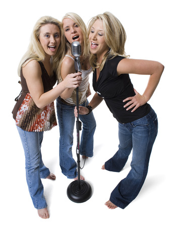 Portrait Of Three Young Women Holding A Microphone And Singing