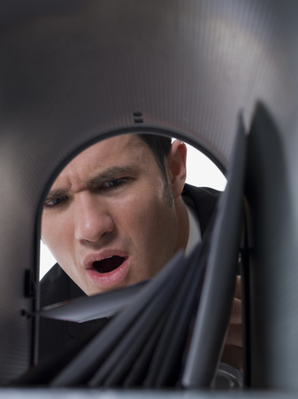 Close-Up Of A Businessman Looking Into A Mailbox