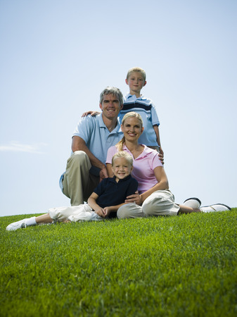 Low Angle View Of A Family Sitting On Grass LANG_EVOIMAGES