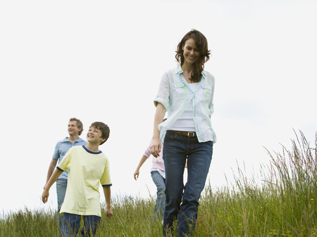 Low Angle View Of A Woman And A Man With Their Son And Daughter In A Field