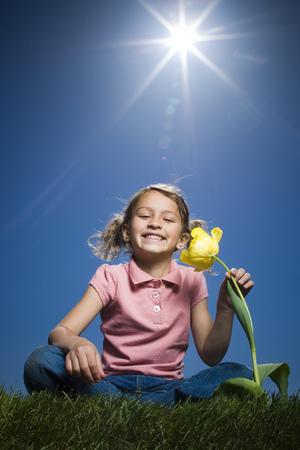 Portrait Of A Girl Sitting Beside A Flower