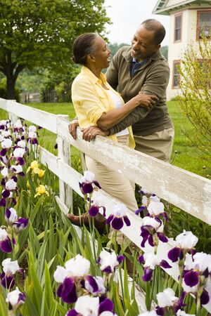 Senior Man And A Senior Woman Standing Near A Fence LANG_EVOIMAGES