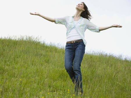 ebullient: Woman With Her Arms Outstretched In A Field