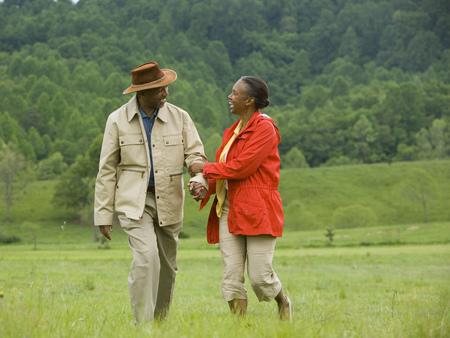 Senior hombre y una mujer mayor caminando en un campo LANG_EVOIMAGES