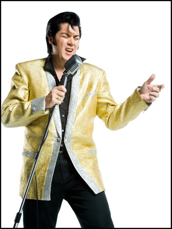 Close-Up Of An Elvis Impersonator Singing Into A Microphone