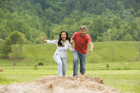 2 way: Portrait Of A Man And A Woman Running On Hay Bales