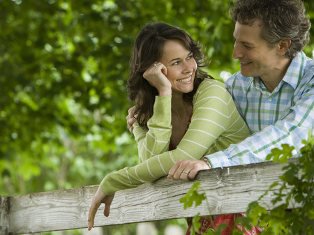Man And A Woman Leaning On A Wooden Fence
