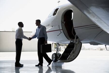 Profile Of Two Businessmen Shaking Hands By An Airplane LANG_EVOIMAGES