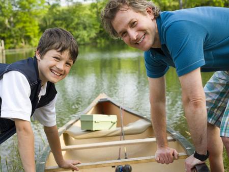 Retrato de un hombre y su hijo inclinado hacia adelante sobre una canoa
