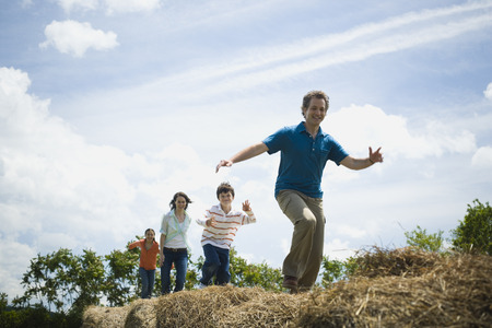 Low Angle View Of A Man And A Woman Jumping With Their Children On Hay Bales