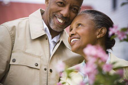 Primer plano de un hombre mayor y una mujer mayor sonriendo detrás de las flores