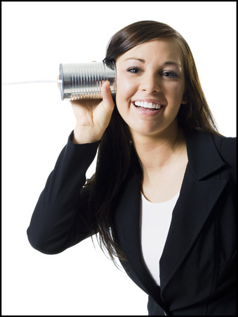 Close-Up Of A Teenage Girl Holding A Tin Can Phone Up To Her Ear LANG_EVOIMAGES