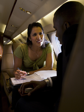 High Angle View Of A Businesswoman And A Businessman Sitting Face To Face In An Airplane And Talking