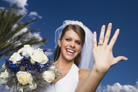 Portrait Of A Bride Showing Her Wedding Ring And Smiling LANG_EVOIMAGES