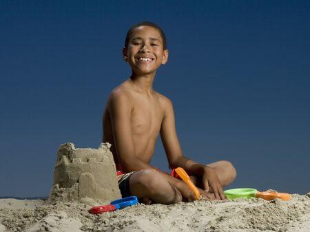 Portrait Of A Boy Sitting Beside A Sand Castle
