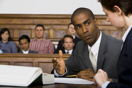 A Male Lawyer Looking At Another Lawyer In A Courtroom