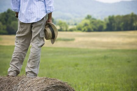 Low Section View Of A Man Standing On A Hay Bale