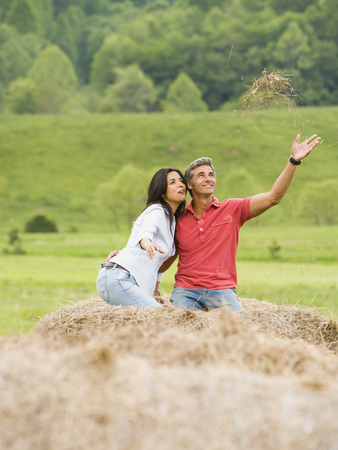 Man And A Woman Sitting On A Hay Bale