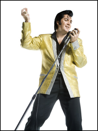 An Elvis Impersonator Singing Into A Microphone