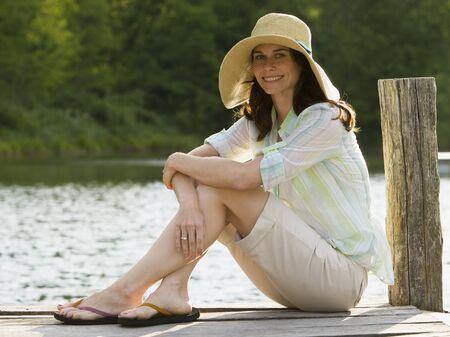 Perfil de una mujer con un sombrero de paja y sentado en un muelle