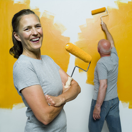 Portrait Of A Senior Woman Holding A Paint Roller With A Senior Man Painting A Wall
