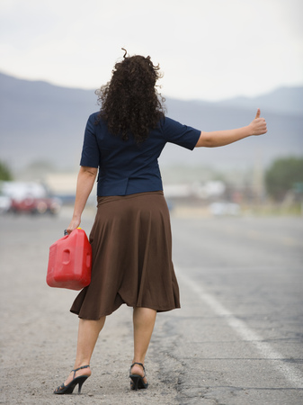 Rear View Of A Young Woman Holding A Gas Can And Hitchhiking LANG_EVOIMAGES